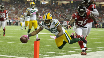 Green Bay Packers wide receiver Greg Jennings (85) dives past Atlanta Falcons free safety James Sanders (36) for a touchdown the fourth quarter of an NFL football game in Atlanta, Georgia, Sunday, Oct. 9, 2011. The Packers won 25-14. (AP Photo/Paul Abell)