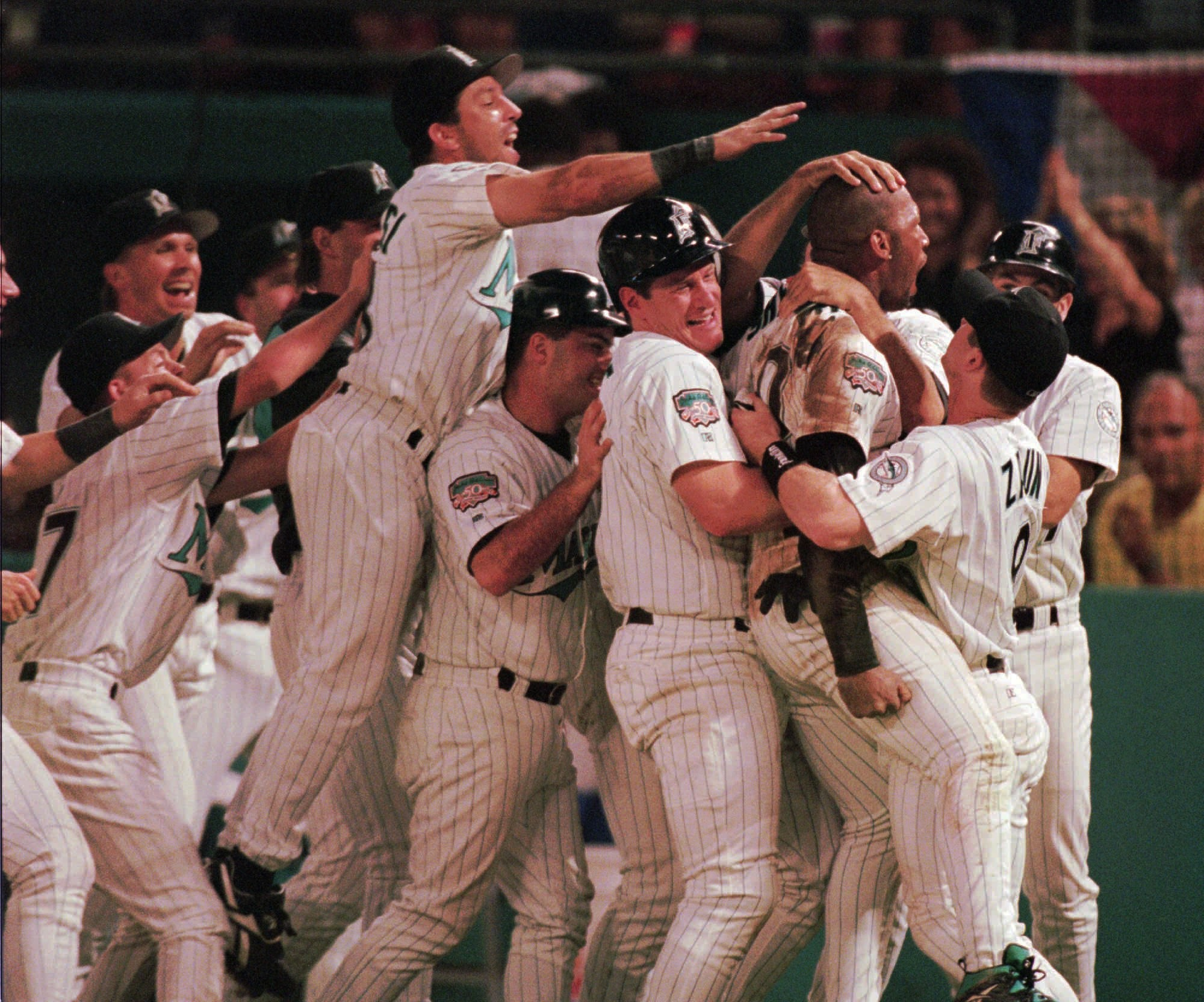 Florida Marlins teammates mob Gary Sheffield, second from right, after he scored the winning run in the bottom of the ninth inning to beat the San Francisco Giants 7-6 in the second game of their divisional series Wednesday, Oct. 1, 1997, in Miami. (AP Photo/Marta Lavandier)