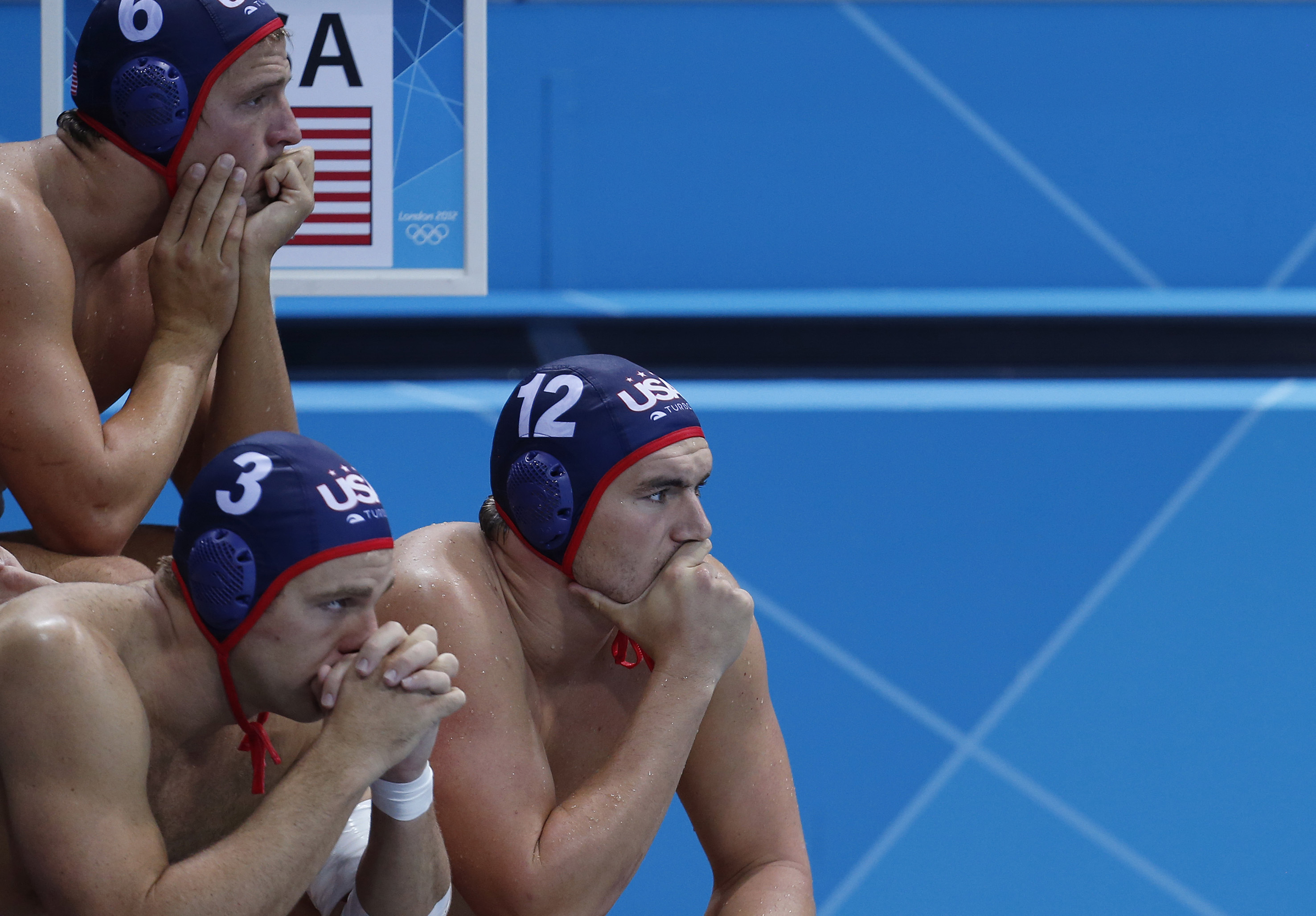Shea Buckner, top left, with teammates Peter Hudnut, left and John Mann of the United States water polo team sit on the bench as they watch the game against Croatia during their men's quarterfinal water polo match at the 2012 Summer Olympics, Wednesday, Aug. 8, 2012, in London. (AP Photo/Alastair Grant)