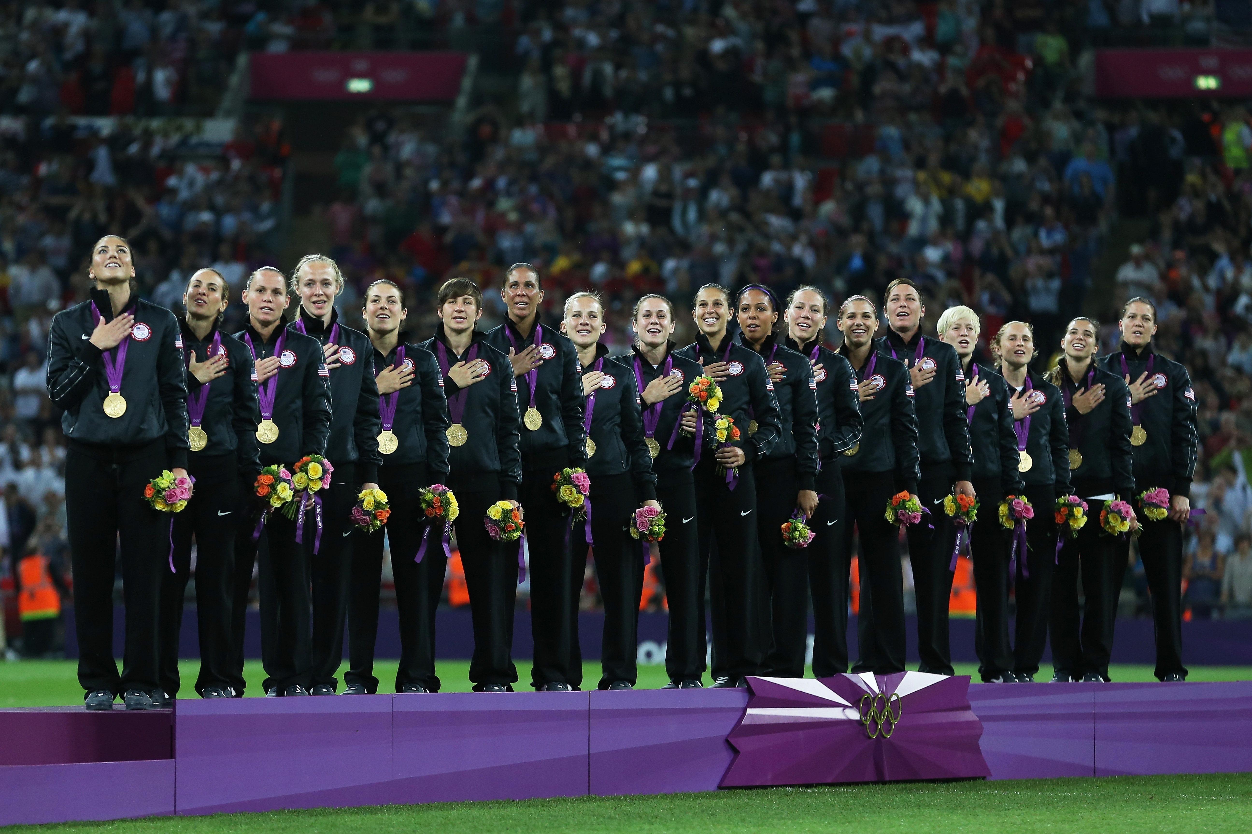 LONDON, ENGLAND - AUGUST 09: The United States women's soccer team listens to the national anthem with the the gold medal after defeating Japan by a score of 2-1 to win the Women's Football gold medal match on Day 13 of the London 2012 Olympic Games at Wembley Stadium on August 9, 2012 in London, England. (Photo by Julian Finney/Getty Images)