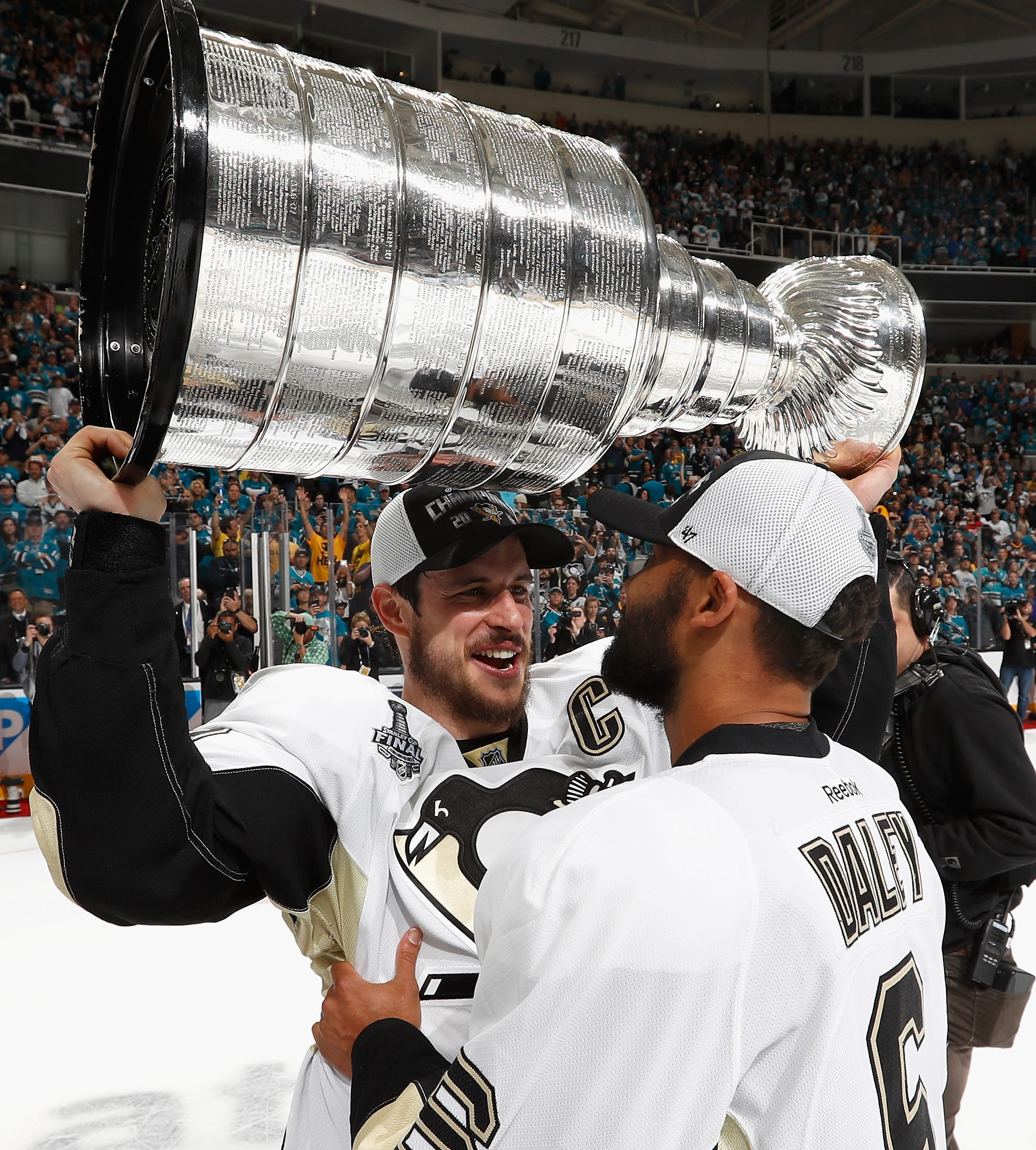 SAN JOSE, CA - JUNE 12: Sidney Crosby #87 of the Pittsburgh Penguins ands off the Stanley Cup to teammate Trevor Daley #6 after the Penguins won Game 6 of the 2016 NHL Stanley Cup Final over the San Jose Sharks at SAP Center on June 12, 2016 in San Jose, California. The Penguins won the game 3-1 and the series 4-2. (Photo by Gregory Shamus/NHLI via Getty Images)